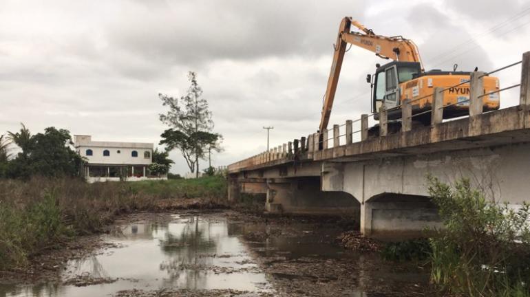 Três caminhões reforçam limpeza dos pilares da Ponte do Gote, em Campos